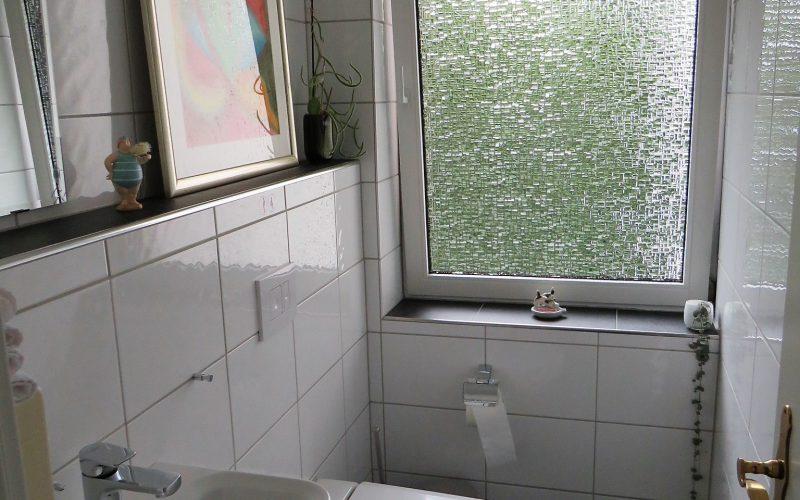 WC mit Waschbecken, weiss gefliest und einem schönen Bild