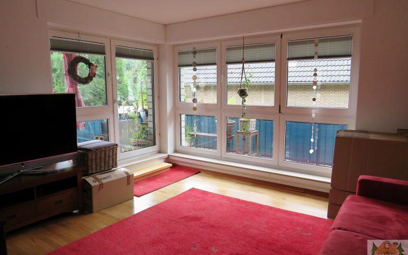 heller Raum mit Parkett und rotem Teppichboden und roter Couch. Man kann hieraus den zweiten Balkon betreten