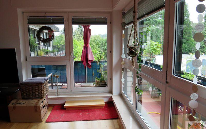 Raum mit Fensterfront über Eck und Balkon über Eck, Aussicht in den Garten