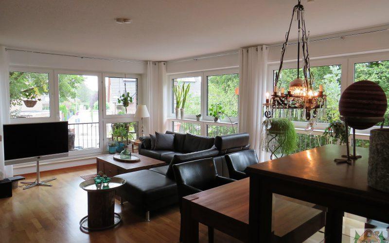 großer Raum mit Essecke und einem großen Sofa, sowie einem umliegenden Balkon