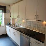 weisse Einbauküche mit dunkler Arbeitsplatte und weissen Fliesen, sowie einem Fenster