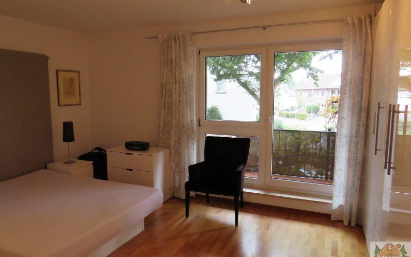 Schlafzimmer mit Parkett und Austritt auf den Balkon
