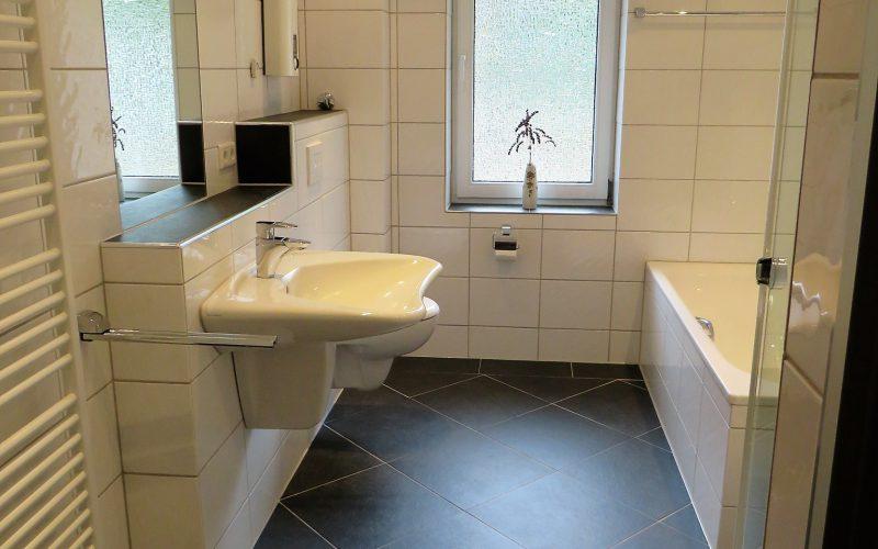 Tageslichtbad mit Badewanne, Dusche, Waschbecken, weiss gefliest an den Wänden, die Böden sind schwarz gefliest
