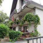 weißes Haus mit begrünten Balkonen und Zufahrt Tiefgarage