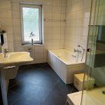 weiß gefliestes, modernes Bad mit Dusche, Wanne, Waschbecken und dunklen Bodenfliesen