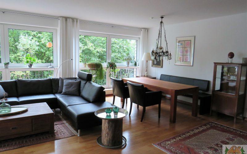 große Fensterfront, Esstisch, Sofa und viele Pflanzen