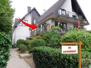 7-Familienhaus mit begrüntem Vorgarten und Schild zu verkaufen